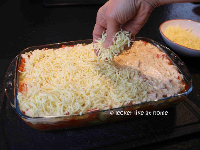 geriebenen Käse auf dem Auflauf verteilen
